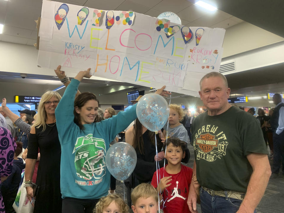 Danny Mather, right, and other family members wait at the Wellington International Airport for the arrival of Mather's pregnant daughter Kristy in Wellington, New Zealand Monday, April 19, 2021. The start of quarantine-free travel was a relief for families who have been separated by the coronavirus pandemic as well as to struggling tourist operators. (AP Photo/Nick Perry)