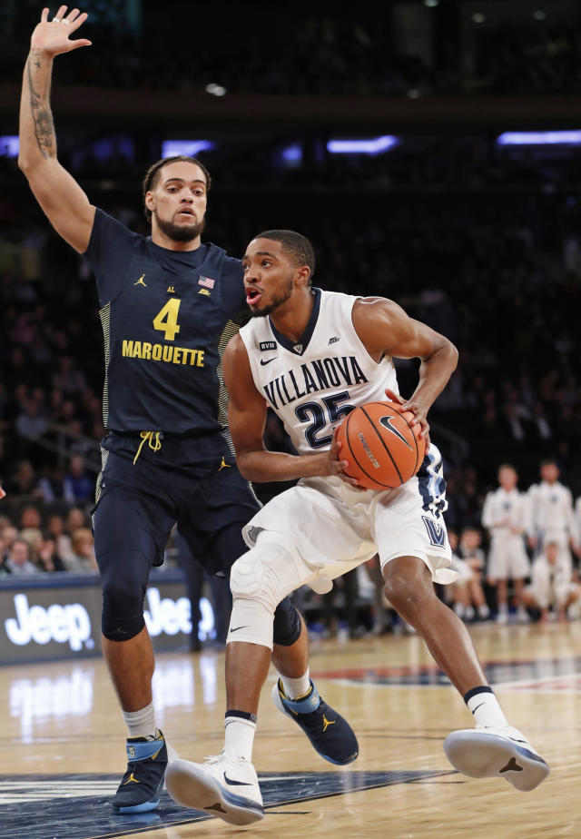 Marquette forward Theo John (4) defends against Villanova guard Mikal Bridges (25) during the first half of an NCAA college basketball game in the quarterfinals of the Big East men's tournament in New York, Thursday, March 8, 2018. (AP Photo/Kathy Willens)