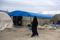 A displaced Syrian woman walks among tents and make-shift homes at the al-Hol camp in northeastern Syria