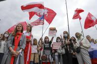 Women with old Belarusian national and American flags march during an opposition rally to protest the official presidential election results in Minsk, Belarus, Saturday, Sept. 5, 2020. Women's marches and demonstrations have become a regular feature of the four weeks of protest that have shaken Belarus following a disputed election that gave Belarusian President Alexander Lukashenko a sixth term in office. (AP Photo)