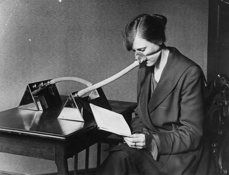"""<p>A woman is seen here reading at a desk while wearing a """"flu mask"""" following an epidemic in 1919.</p>"""