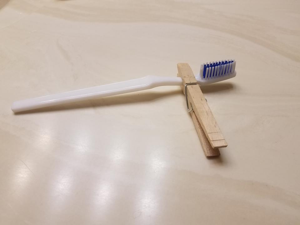 Using a clothespin to hold a toothbrush