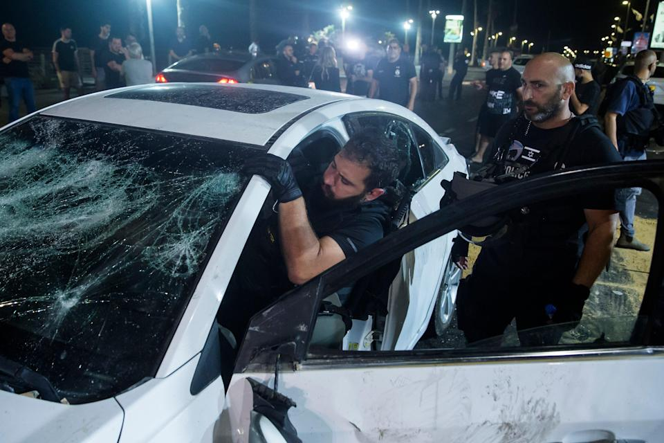 An Israeli police officer inspects the car of an Israeli Arab man who was attacked and seriously injured by a mob in Bat YamAmir Levy/Getty Images
