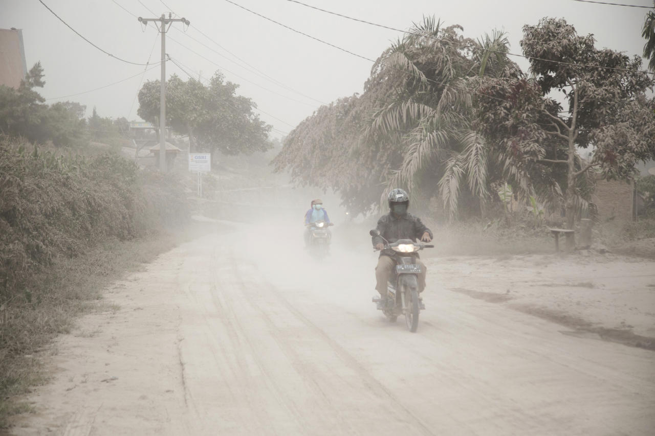 Motorists ride on a road covered in volcanic ash from the eruption of Mount Sinabung in Gurukinayan, North Sumatra, Indonesia, Monday, Feb. 19, 2018. Rumbling Mount Sinabung on the Indonesian island of Sumatra has shot billowing columns of ash more than 5,000 meters (16,400 feet) into the atmosphere and hot clouds down its slopes. (AP Photo/Endro Rusharyanto)