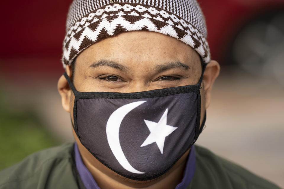 A Muslim man wearing a protective mask prepares to pray outside the closed National Mosque while celebrating Eid al-Fitr, the Muslim festival marking the end the holy fasting month of Ramadan, amid the coronavirus outbreak, in Kuala Lumpur, Malaysia, Sunday, May 24, 2020. (AP Photo/Vincent Thian)