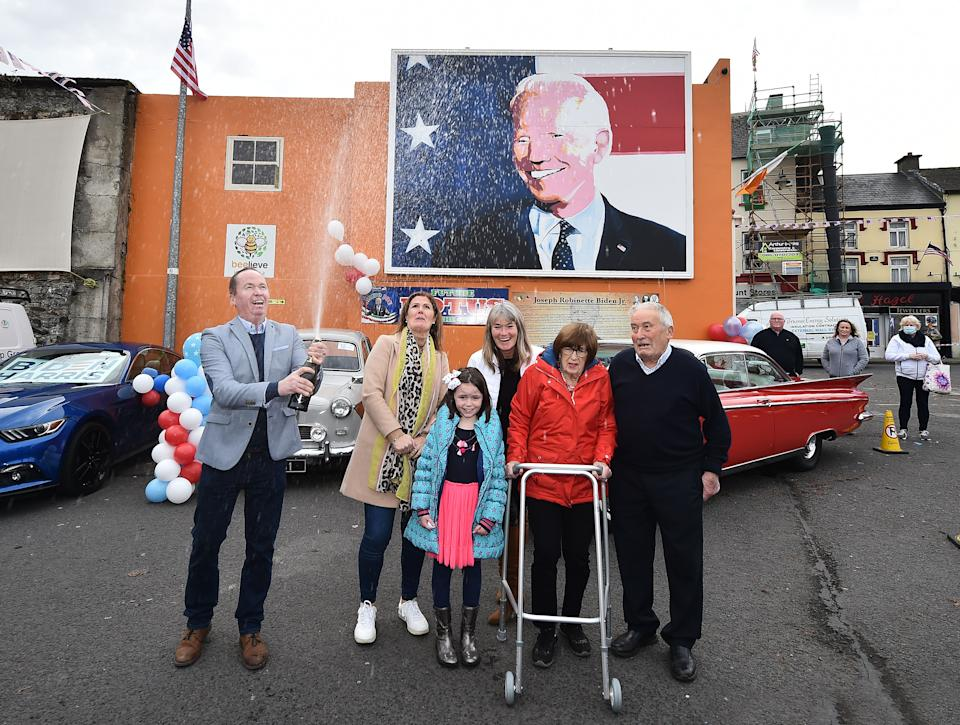 Joe Blewitt a cousin of Joe Biden sprays a bottle of champagne along with family members underneath a mural of Presidential candidate Joe Biden as locals celebrate (Nov. 7) in anticipation of Biden being elected as the next US President in Ballina, Ireland. Joe Biden whose distant relatives hail from the County Mayo town of Ballina has visited the town twice before as the former Vice President. Photo: Charles McQuillan/Getty Images