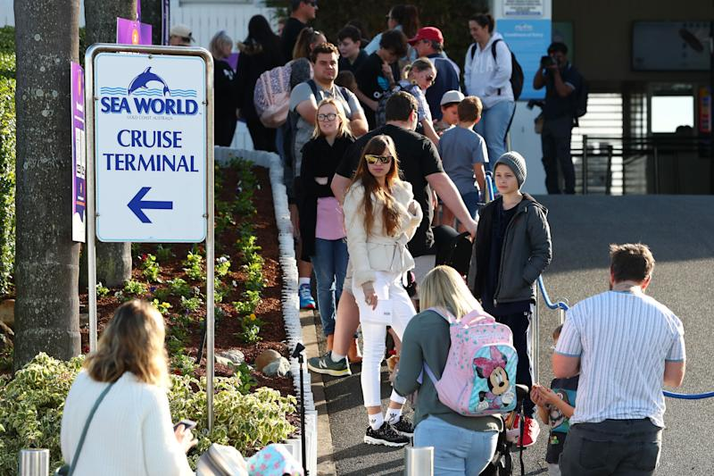 GOLD COAST, AUSTRALIA - JUNE 26: Crowds line up to enter Seaworld on June 26, 2020 in Gold Coast, Australia. Sea World has reopened to the public with extra safety and hygiene measures in place following its temporary closure on 23 March 2020 due to the COVID-19 pandemic. Visitors to Sea World must observe physical distancing rules and provide details for contact tracing purposes. Increased sanitisation of high touch areas throughout the park have been introduced along with contactless payments. (Photo: Chris Hyde via Getty Images)