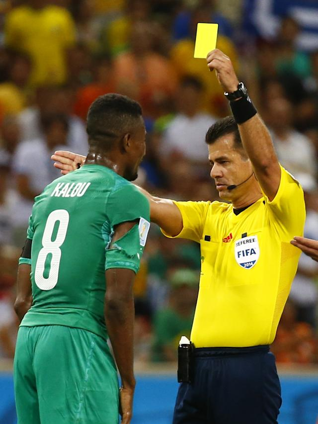 Ivory Coast's Kalou receives a yellow card from Referee Vera of Ecuador during their 2014 World Cup Group C soccer match against Greece at the Castelao arena in Fortaleza