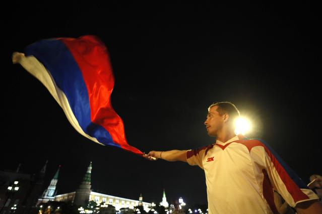 Soccer Football - World Cup - Group A - Russia vs Egypt - Moscow, Russia June 20, 2018 A Russian fan waves a national flag a he celebrates victory after the match. REUTERS/Maxim Shemetov
