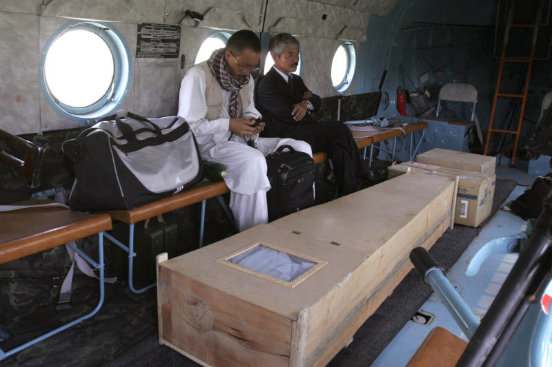FILE -In this Thursday, Aug. 28, 2008, photo, Japanese doctor Tetsu Nakamura, center right, sits with unidentified man, near the casket of Japanese aid worker Kazuya Ito, who was killed in Nangarhar province, in a helicopter bound for Kabul. The Japanese physician and aid worker in eastern Afghanistan died of his wounds after an attack Wednesday, Dec. 4, 2019, that also killed five Afghans, including the doctor's bodyguards, the driver and a passenger, a hospital spokesman said. (AP Photo/Rahmat Gul, File)