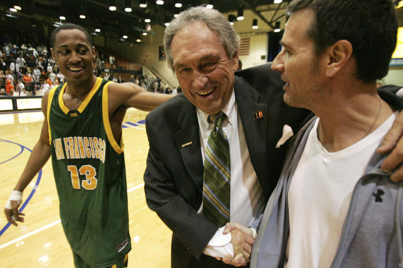 FILE - In this Saturday, Feb. 2, 2008, file photo, San Francisco head coach Eddie Sutton shakes the hand of Terry Anzaldo as Myron Strong, left, smiles after San Francisco defeats Pepperdine 88-85 in an NCAA college basketball game to give Sutton his 800th win, in Malibu, Calif. Sutton, the Hall of Fame basketball coach who led three teams to the Final Four and was the first coach to take four schools to the NCAA Tournament, died Saturday, May 23, 2020. He was 84. (AP Photo/Jeff Lewis, File)