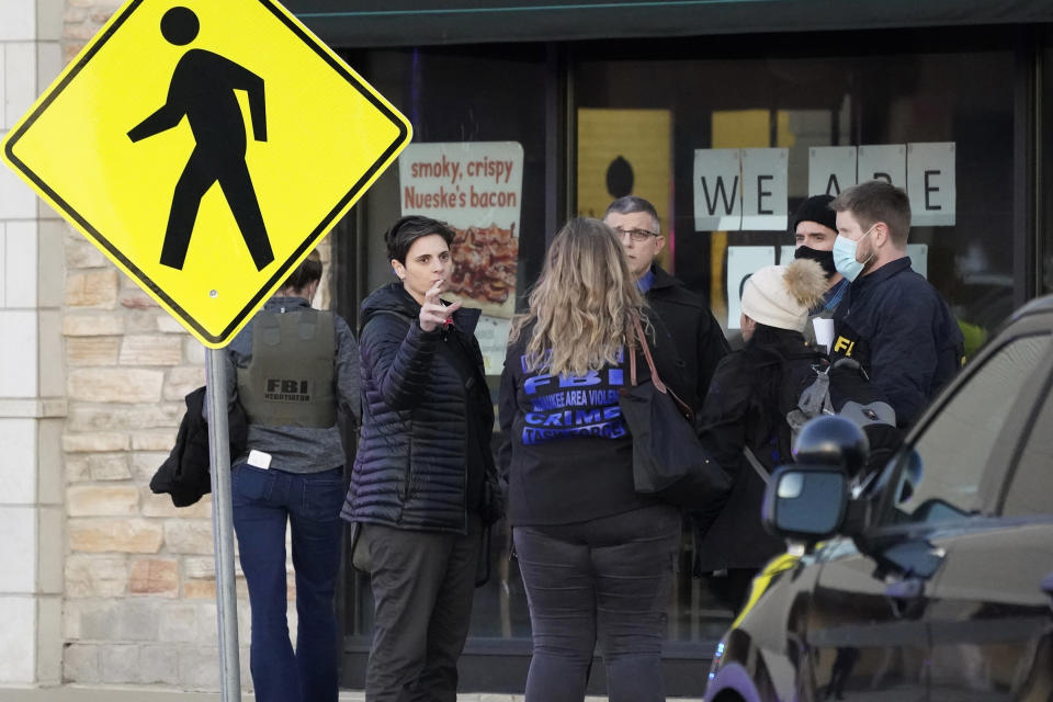 FBI officials convene after a shooting at the Mayfair Mall, Friday, Nov. 20, 2020, in Wauwatosa, Wis. Multiple people were shot Friday afternoon at the mall. Wauwatosa Mayor Dennis McBride says in a statement that a suspect remains at large after the shooting at Mayfair Mall. (AP Photo/Nam Y. Huh)