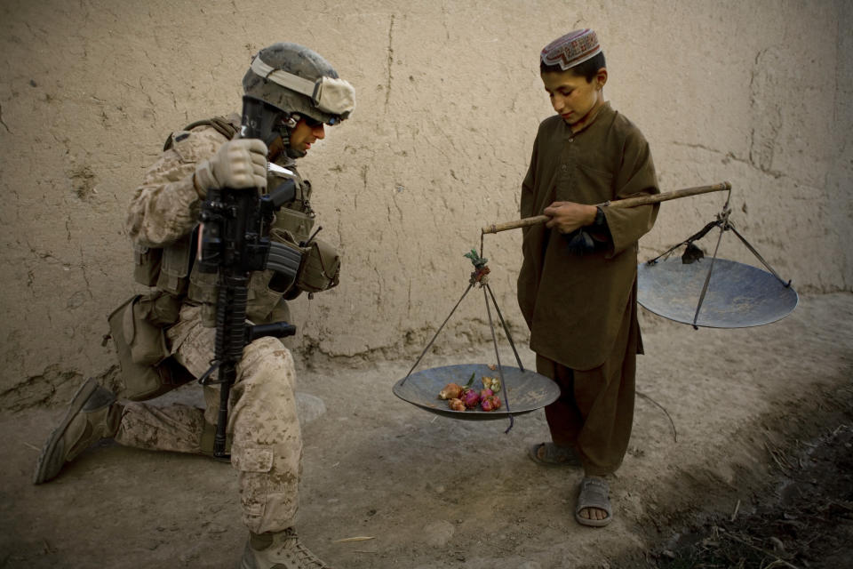 FILE - In this Nov. 3, 2010 file photo, First Sgt. Yomen English, of Brookland, Ark., with India company, 3rd Battalion 5th Marines, First Marine Division, talks to a boy during a patrol, in Sangin, Afghanistan. (AP Photo/Dusan Vranic, File)