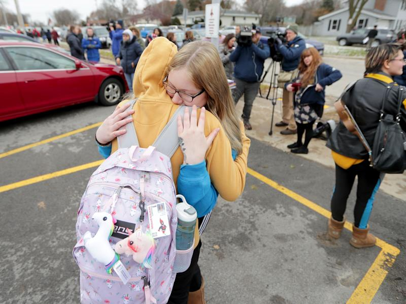 Alexis Grady, facing, a 17-year-old senior, hugs her friend Arissa Goodman an 18-year-old senior, outside Waukesha South High School in Waukesha, Wis., on Monday, Dec. 2, 2019. Gunshots were exchanged between a student and a school resource officer inside Waukesha South High School, according to school officials.