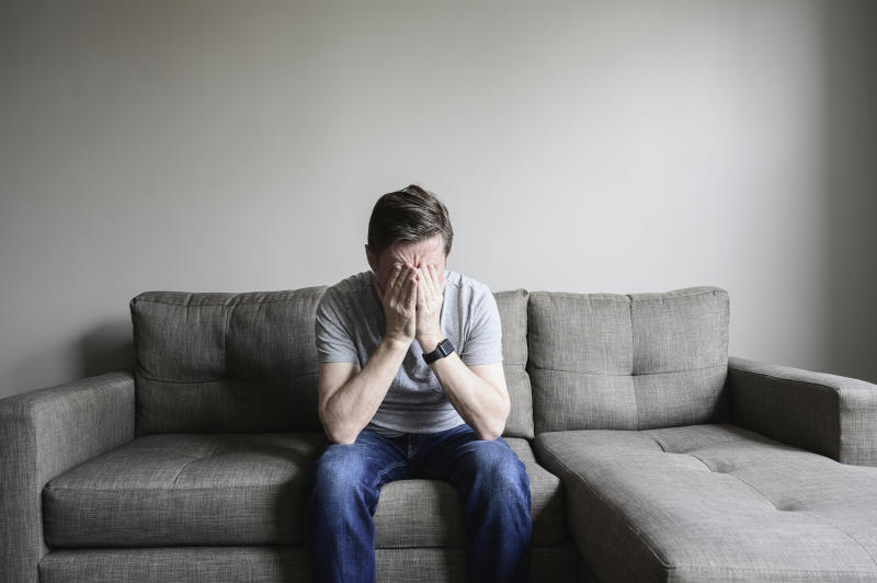 A man looking distressed on a couch, with his face in his hands.