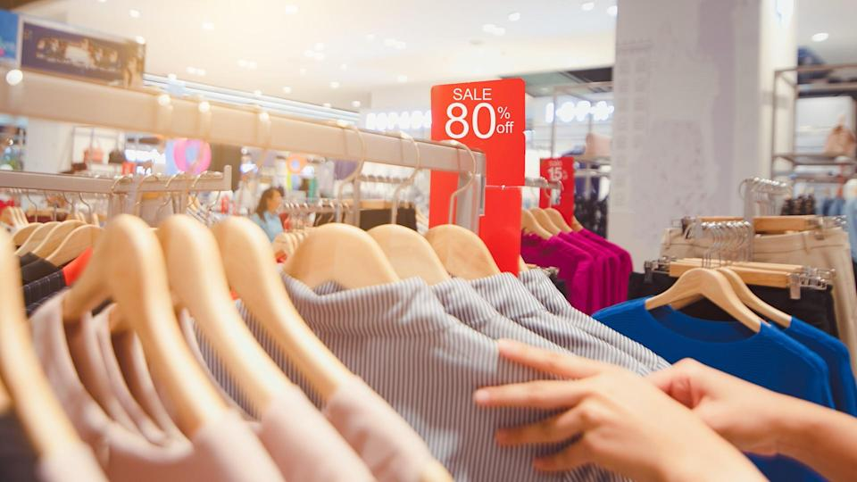 Big sale tag announcement at clothes shop, Looking for brightly colored clothes on hangers, Choose to buy clothes.