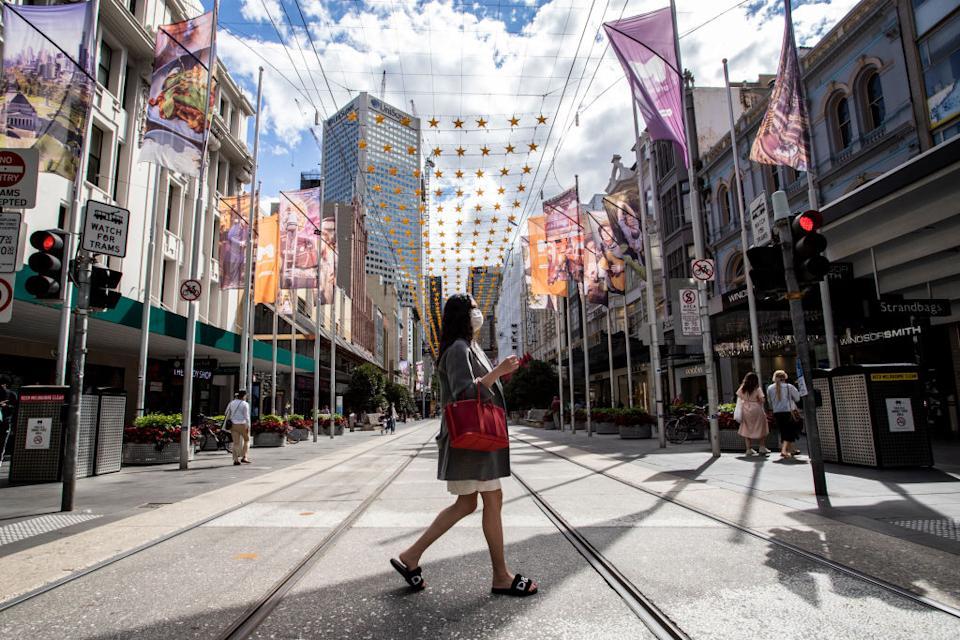 A woman wearing a face mask seen crossing the Bourke Street Mall in Melbourne.