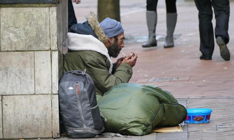 A homeless man sitting on the pavement