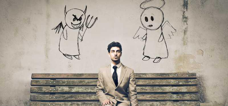 Man sitting on a bench with drawing of angel and demon over his shoulders.