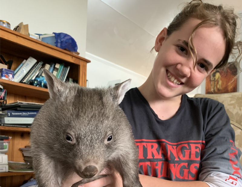 Eliza Hungerford wearing a Stranger Things top holds up a juvenile wombat.