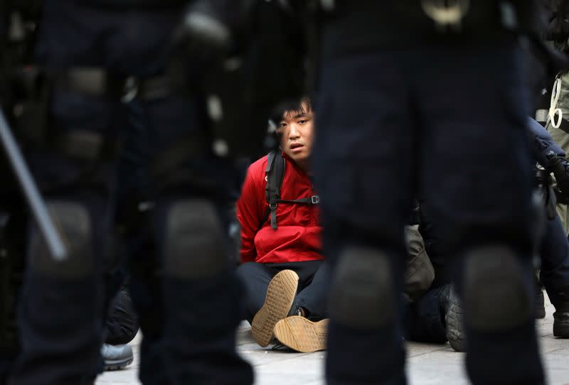 """A protester is detained by riot police during the """"Lest We Forget"""" rally in Hong Kong"""
