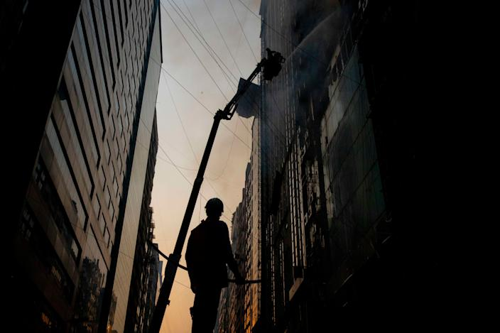 Bangladeshi firefighter work on ladders to eclipse a blaze in a building Banani. A huge fire split through an office building at least 21 deaths in Dhaka, Bangladesh. (Photo: K M Asad/LightRocket via Getty Images)