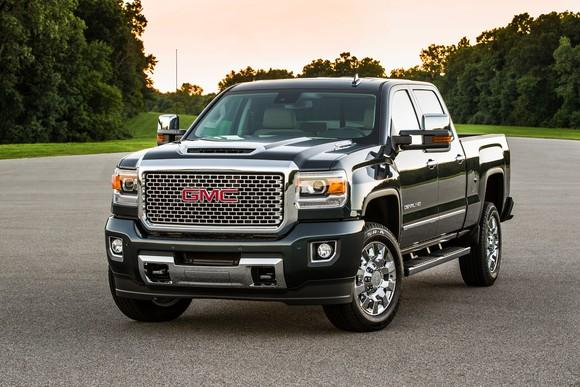A black 2017 GMC Sierra 2500 Denali HD, parked near a wooded area.