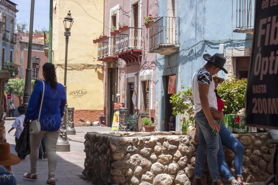 Guanajuato, Mexico, September 05, 2018: small square surrounded by colorful buildings with people around and a boy in a cowboy hat. Travel concept