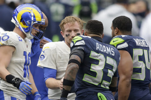 Seattle Seahawks strong safety Jamal Adams (33) talks with Los Angeles Rams quarterback John Wolford after Wolford was injured and was leaving during the first half of an NFL wild-card playoff football game, Saturday, Jan. 9, 2021, in Seattle. (AP Photo/Scott Eklund)