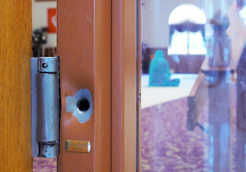 In this July 27, 2013, a worshipper meditates in a prayer hall where a bullet hole in the door jamb serves as a reminder of a shooting rampage last year in which a gunman killed six people at the Sikh Temple of Wisconsin in Oak Creek, Wis. Monday is the one-year anniversary that members say they'll mark with solemn religious rites and a candlelight vigil. (AP Photo/Dinesh Ramde)