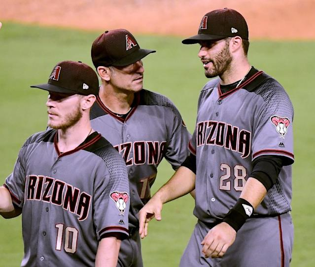 J.D. Martinez (R) of the Arizona Diamondbacks is congratulated by manager Torey Lovullo after a four home-run game to beat the Los Angeles Dodgers 13-0, at Dodger Stadium in Los Angeles, California, on September 4, 2017 (AFP Photo/Harry How)