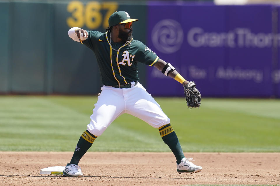 Oakland Athletics second baseman Josh Harrison throws to first base to turn a double play on a ground ball hit into by Seattle Mariners' Ty France during the third inning of a baseball game in Oakland, Calif., Tuesday, Aug. 24, 2021. (AP Photo/Jeff Chiu)