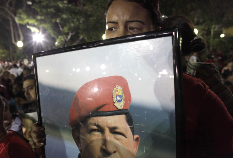 A supporter of Venezuela's President Hugo Chavez cries as she holds a picture of Venezuela's late President Hugo Chavez, as Chavistas gather in Bolivar square to mourn Chavez's death in Caracas, Venezuela, Tuesday, March 5, 2013. Venezuela's Vice President Nicolas Maduro announced that Chavez died on Tuesday at age 58 after a nearly two-year bout with cancer. During more than 14 years in office, Chavez routinely challenged the status quo at home and internationally. He polarized Venezuelans with his confrontational and domineering style, yet was also a masterful communicator and strategist who tapped into Venezuelan nationalism to win broad support, particularly among the poor. (AP Photo/Ariana Cubillos)