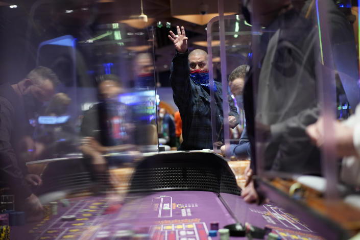 FILE - In this March 25, 2021, file photo, people play craps while wearing masks and between plexiglas partitions as a precaution against the coronavirus at the opening night of the Virgin Hotels Las Vegas in Las Vegas. On Saturday, May 1, casino capacity limits in Las Vegas increase to 80% and person-to-person distancing drops from 6 feet (1.8 meters) to 3 feet (0.9 meters). (AP Photo/John Locher, File)