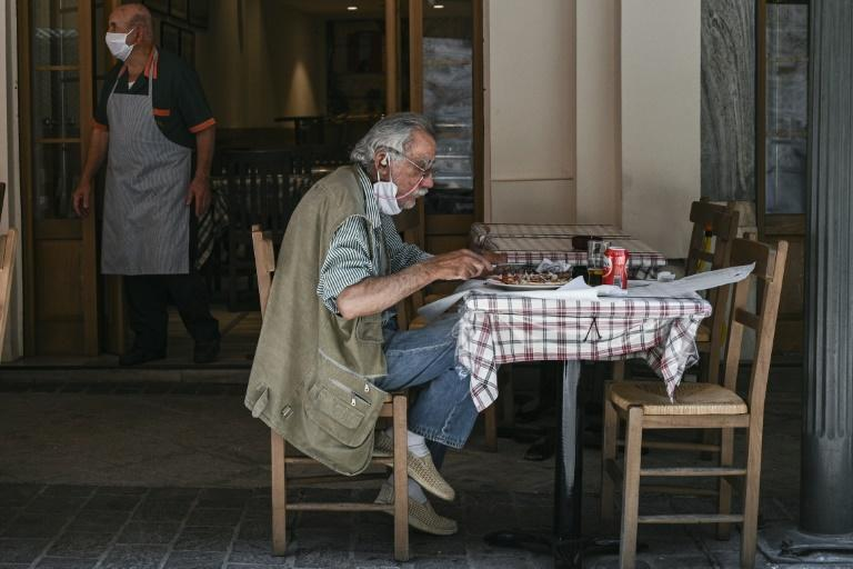 Slowing infection rates have allowed restaurants in Greece to reopen a week ahead of schedule, but only for outdoor service (AFP Photo/ARIS MESSINIS)