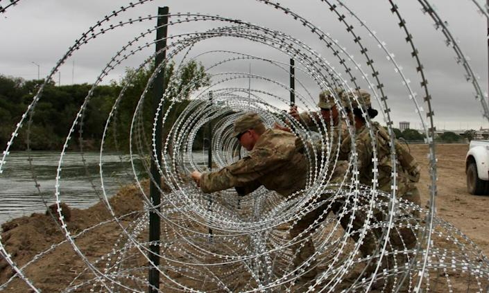 "<span class=""element-image__caption"">Soldiers install barbed wire fences on the banks of the Rio Grande in Laredo, Texas on 18 November. </span> <span class=""element-image__credit"">Photograph: Thomas Watkins/AFP/Getty Images</span>"