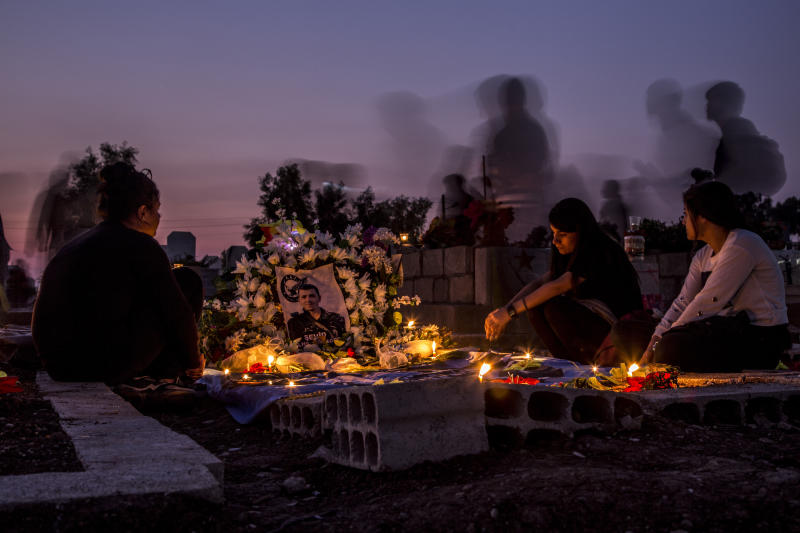 Relatives visit a grave of Syrian Democratic Forces fighter recently killed during Turkish offensive, in the town of Qamishli, north Syria, Thursday, Oct. 31, 2019. (AP Photo/Baderkhan Ahmad)
