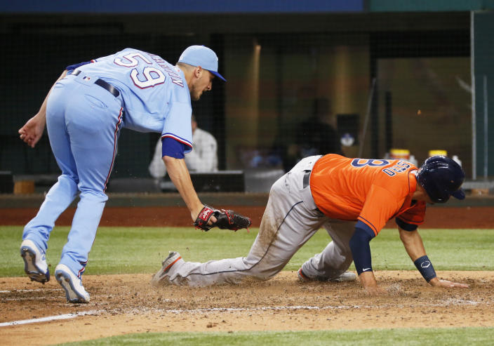 Houston Astros' Jason Castro, right, avoids a tag by Texas Rangers relief pitcher Brett de Geus, left, as he scores on a wild pitch during the eighth inning of a baseball game in Arlington, Texas, Sunday, May 23, 2021. (AP Photo/Ray Carlin)