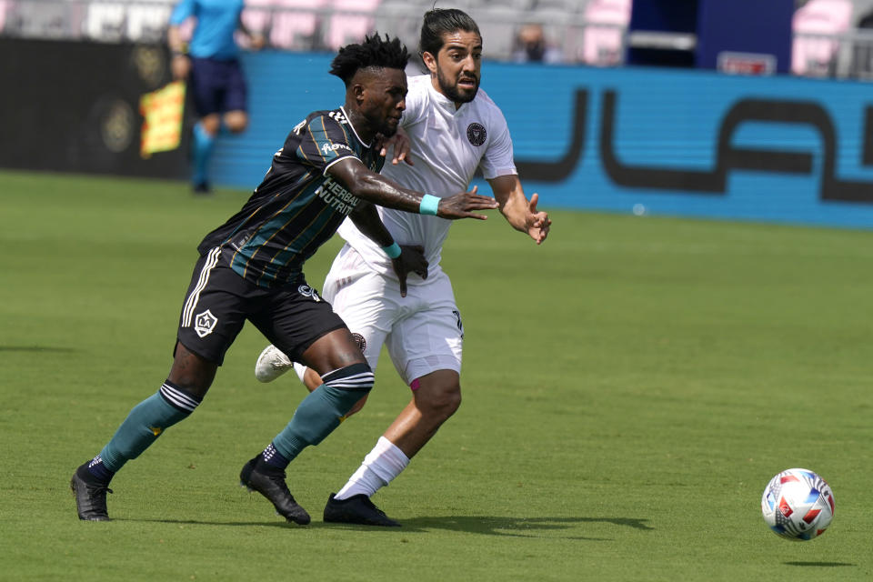 LA Galaxy defender Oniel Fisher, left, and Inter Miami midfielder Rodolfo Pizarro go for the ball during the first half of an MLS soccer match, Sunday, April 18, 2021, in Fort Lauderdale, Fla. (AP Photo/Lynne Sladky)