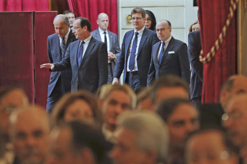 French President Francois Hollande, second from left, talks with his foreign minister Laurent Fabius, left, as they arrive followed by government members for a New Year wishes ceremony for diplomats at the Elysee Palace in Paris, Friday Jan. 11, 2013.(AP Photo/Philippe Wojazer/Pool)