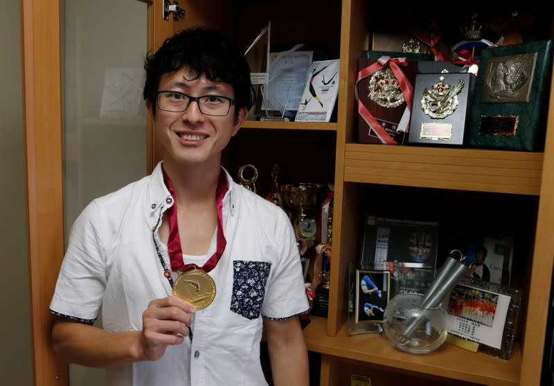 Former Japanese Olympic Trampolinist Tetsuya Sotomura poses with one of the medals he won, amid the coronavirus disease (COVID-19) pandemic in Saitama