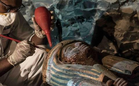 Egyptian archaeologist restoring a wooden sarcophagus at a newly-uncovered ancient tomb for a goldsmith in Luxor - Credit: KHALED DESOUKI/AFP/Getty Images