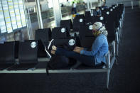 A passenger, wearing a face mask to protect against the spread of coronavirus, sits before boarding her flight at the Zaventem international airport during the partial lifting of coronavirus COVID-19 lockdown regulations in Brussels, Monday, June 15, 2020. Borders opened up across Europe on Monday after three months of coronavirus closures that began chaotically in March. (AP Photo/Francisco Seco)