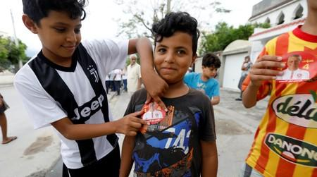 A boy puts a sticker of presidential candidate Nabil Karoui on his friend's t-shirt during a campaign in Tunis