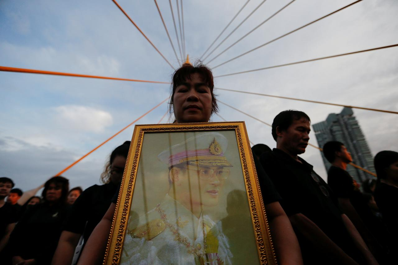 A woman holds a portrait of late Thai King Bhumibol Adulyadej during an event to mark his birthday at Bhumibol Bridge over Chao Phraya river in Bangkok, Thailand December 5, 2016. REUTERS/Jorge Silva