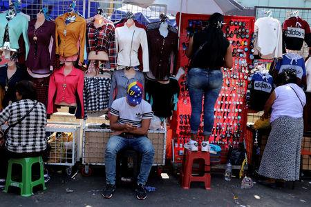 A migrant from Venezuela, sells clothing at Gamarra textile cluster in Lima's district of La Victoria in Lima