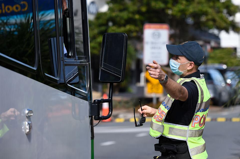 Police are seen directing motorists at the Coolangatta border check point on Griffith St in Gold Coast, Australia.