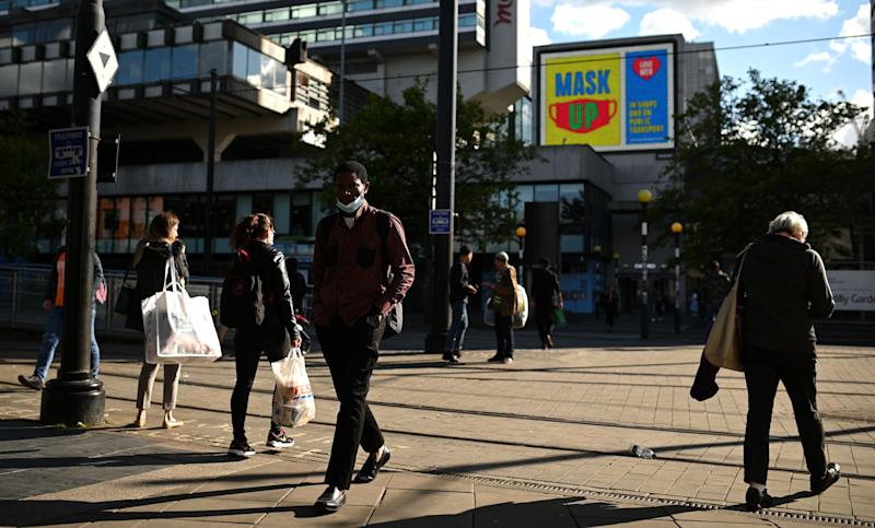 "A man wears a face mask under his chin as he walks near a sign urging people ""Mask up"" in Manchester, northwest England on August 3, 2020, following a rise in the number of COVID-19 cases in the region. - Britain on Friday ""put the brakes on"" easing lockdown measures and imposed new rules on millions of households in northern England, following concerns over a spike in coronavirus infections. The government increased regional lockdown measures -- under which people from different households are banned from meeting indoors -- for some four million people across Greater Manchester and parts of Lancashire and Yorkshire. (Photo by Oli SCARFF / AFP) (Photo by OLI SCARFF/AFP via Getty Images)"