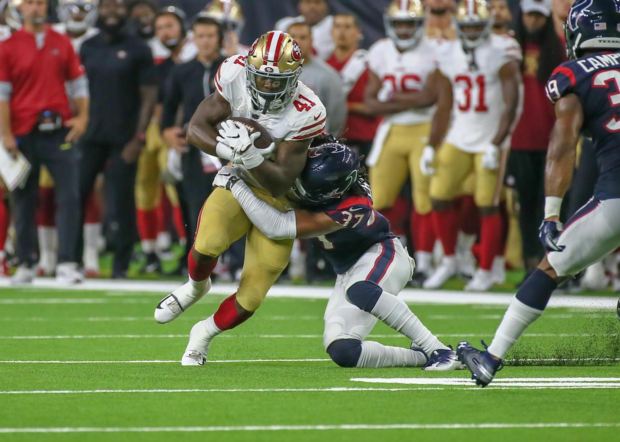 San Francisco 49ers running back Jeff Wilson gets tackled by Houston Texans defensive back Andre Chachere in a preseason game featuring lots of questionable flags. (Getty Images)