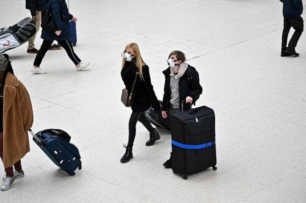 PHOTO: Travelers wearing protective face masks pull their suitcases while walking across the concourse at London Victoria train station in central London, U.K., on March 3, 2020. (Justin Tallis/AFP via Getty Images)